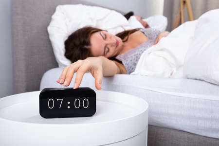 Young Woman Sleeping On Bed Turning Off Alarm Clock In Bedroom Banco de Imagens