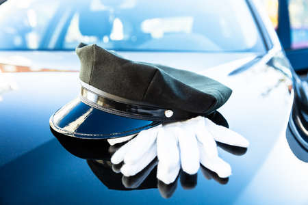 Black Chauffeur's Cap And Pair Of White Hand Gloves On Car Bonnet Stockfoto