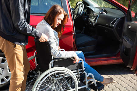 Close-up Of Man With Her Wife Sitting On Wheelchair Moving With Car
