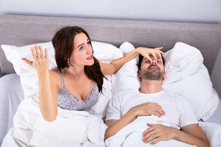 Disturbed Young Woman Holding Her Husbands Nose To Stop Him From Snoring On Bed