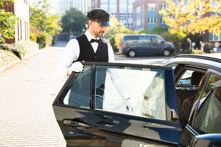 Close-up Of Mans Hand Opening Car Door While Smiling Young Woman Sitting In Car