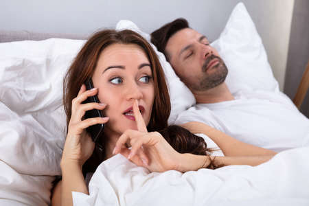 Young Woman Talking Privately On Mobile Phone While Her Husband Sleeping On Bed In Bedroom