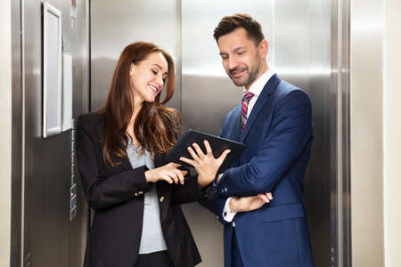 Smiling Young Businesswoman And Businessman Discussing While Using Digital Tablet Standing Near Elevator