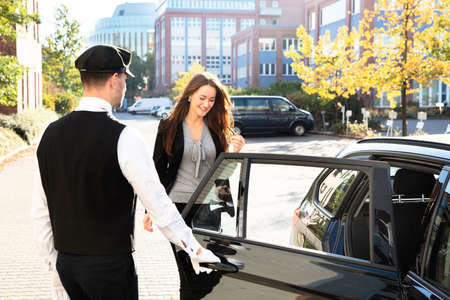 Chauffeur Opening Private Car Door For Businesswoman Stock fotó