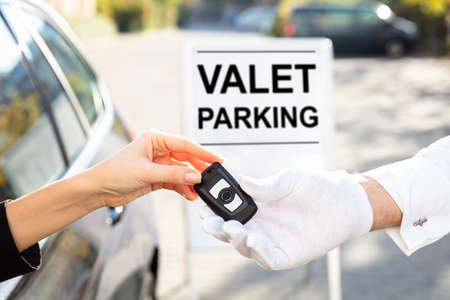 Woman's Hand Giving Car Key To Male Valet Near Valet Parking Sign Stock Photo