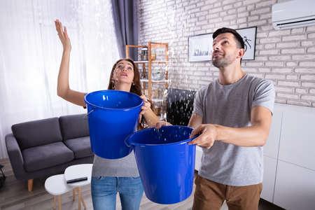 Jeune mari et femme avec seau bleu la collecte de l'eau du plafond endommagé dans la salle de séjour