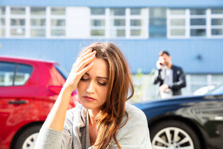 Young Depressed Female Driver After Traffic Accident Sitting On Road