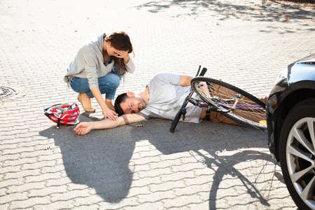 Young Woman Looking At Unconscious Male Cyclist Lying On Street After Accident Near Car