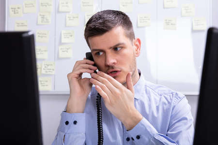 Young Businessman Talking On Landline Phone At Office