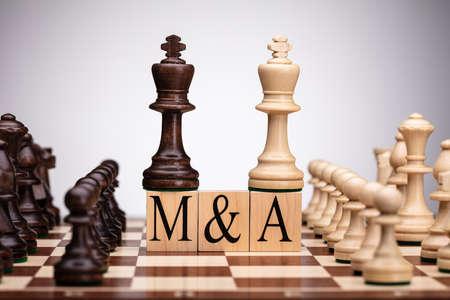 Nahaufnahme von König Schachfiguren auf Holzblöcken mit Fusionen und Übernahmen