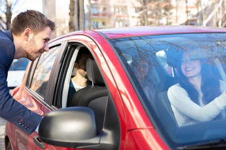 Sonriente joven hablando con una señora sentada dentro del coche Foto de archivo