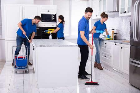 Gruppo di giovani bidelli in uniforme che puliscono la cucina a casa