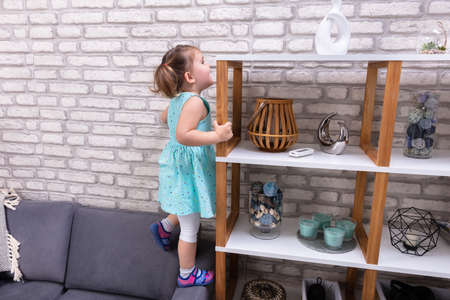 Cute Toddler Girl Standing On Sofa And Reaching For Toys On Shelf