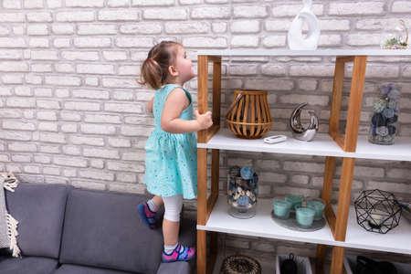 Linda niña de pie en el sofá y alcanzar juguetes en el estante