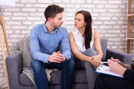 Young Couple Sitting With Female Consultant In Office Stock Photo