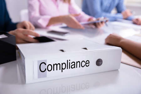 Businesspeople Sitting Near Compliance Documents Over Reflective Desk
