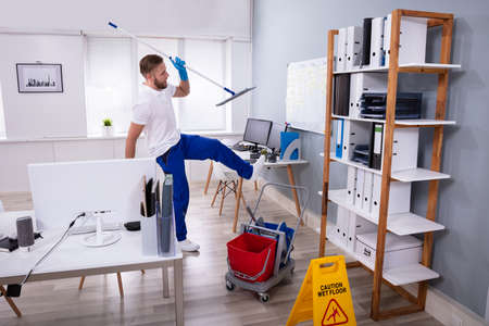 Man Janitor Slipping While Mopping Floor In Modern Office