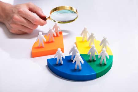 Businesspeople Analyzing Market Segment Using Magnifying Glass