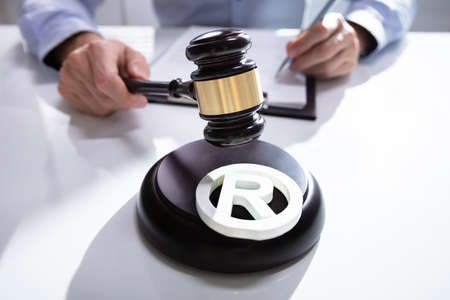 Close-up Of Judge Striking Mallet On Trademark Copyright Symbol