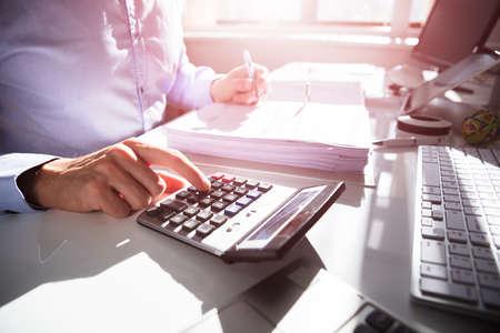 Geschäftsperson, die Rechnung mit dem Taschenrechner am Schreibtisch berechnet