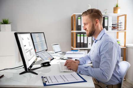 Homme d'affaires calculant la facture électronique en ligne sur l'ordinateur au bureau