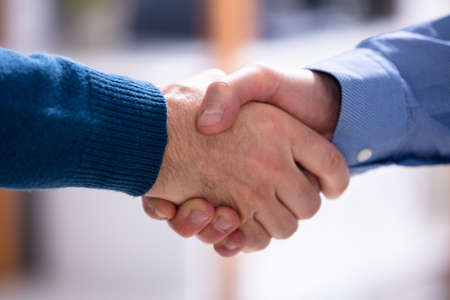 Close-up Of Business Partners Shaking Hands In Office