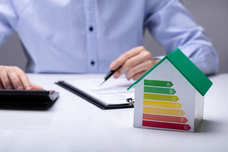 House With Energy Efficiency Rate In Front Of Businesspeople Working In Office While Using Calculator Stock Photo