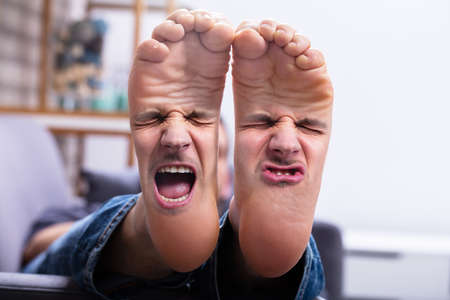 Close-up Of Man's Feet With Painful Facial Expression