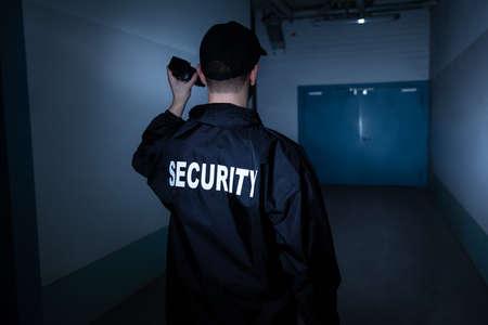 Rückansicht eines männlichen Wachmanns mit Taschenlampe im Korridor Standard-Bild