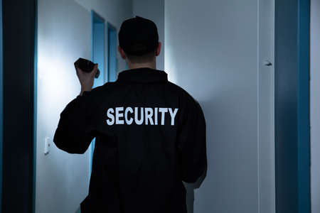 Rear View Of Male Security Guard With Flashlight Standing In Corridor Of The Building