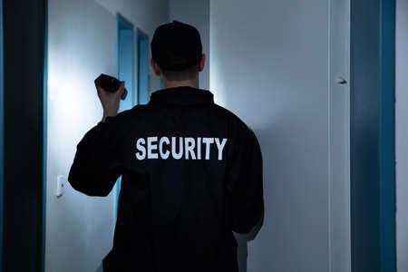 Vista trasera del guardia de seguridad masculino con linterna de pie en el pasillo del edificio