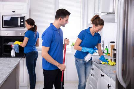 Grupo de jóvenes conserjes en cocina de limpieza uniforme en casa Foto de archivo