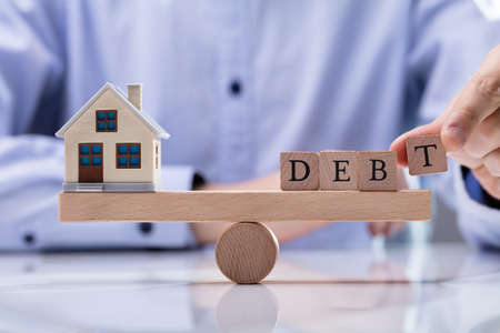 Close-up Of Businessmans Hand Putting Word Debt On Wooden Seesaw To Balancing Model House Stock fotó