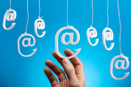Human's Hand Holding Hanging Email Icons Against Blue Background Foto de archivo