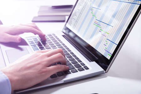 Close-up de empresario analizando el diagrama de Gantt en el portátil en la oficina Foto de archivo