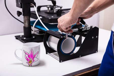 Man afdrukken op koffiemokken in werkplaats Stockfoto