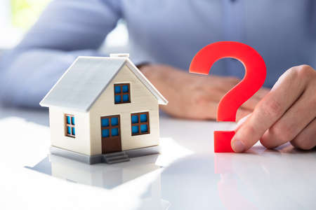 Man Holding Question Mark Next To House Model