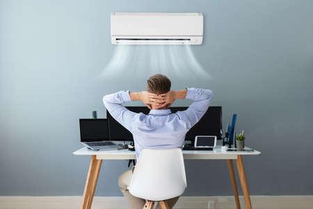 Gelukkig zakenman ontspannen op kantoor met airconditioning