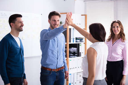 Two Smiling Young Male And Female Businesspeople Giving High Five In Office Imagens