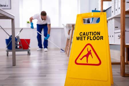 Männlicher Hausmeister mit Mopp, der modernen Büroboden säubert