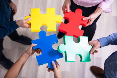 Ein erhöhter Blick auf die Hände, die ein buntes Puzzle halten
