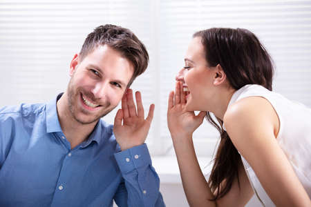 Portrait Of Happy Woman Whispering Secret Or Interesting Gossip To Handsome Man In His Ear Banque d'images