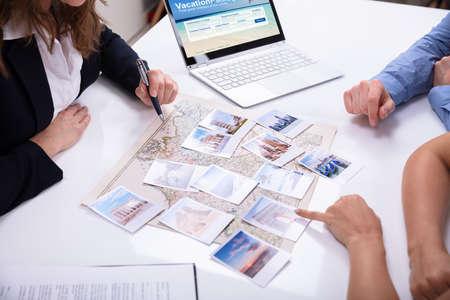 Weibliches Reisebüro, das einem jungen Paar Informationen für ein Urlaubspaket gibt