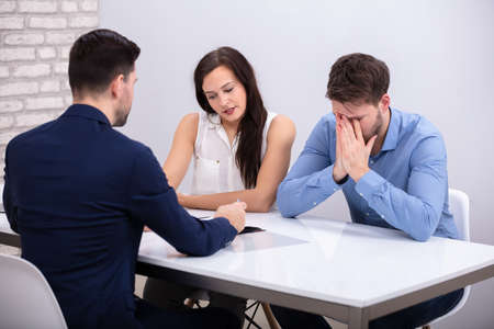 Rear View Of Financial Advisor Sitting With Depressed Young Couple