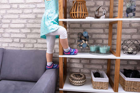 Close-up Of Small Girl Trying To Climb On Shelf At Home 写真素材