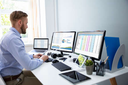 Businessman Working With Spreadsheets On Desktop Computer