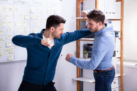 Close-up Of Businessmen Getting Into A Fight Woman Trying To Separate Them In Office Imagens