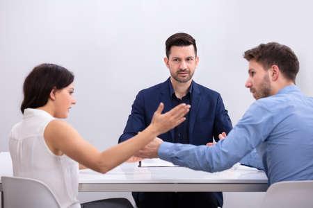 Junges Paar streitet sich vor dem Richter im Gerichtssaal Standard-Bild