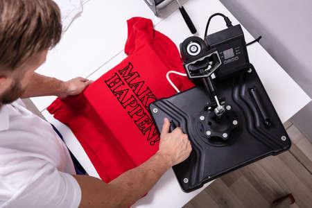 Uomo che stampa su t-shirt in officina Archivio Fotografico