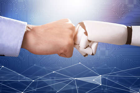 Robot And Human Hand Making Fist Bump On Blue Digital Backdrop